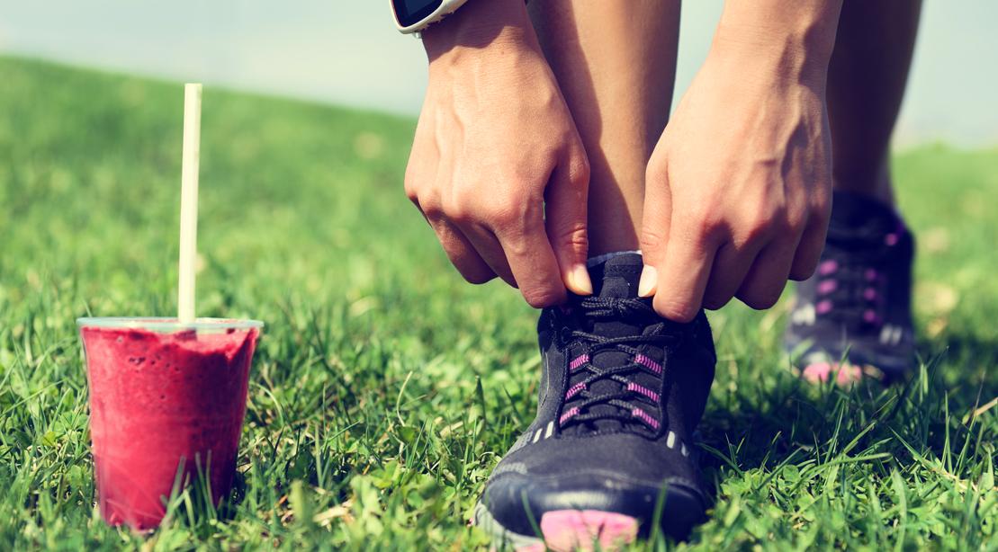 Female-Athlete-Tying-Sneaker-Laces-Grass-Field