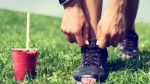 Female-Athlete-Tying-Sneaker-Laces-Grass-Field