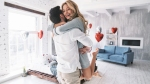 Female-Hugging-Male-Romantic-Couple-Valentines-Day-Heart-Shaped-Balloons-Filled-Room