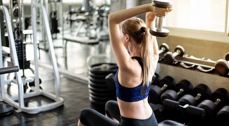Fit female working out her upper body and arms with the tricep exercise the seated overhead dumbbell tricep extension