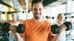 Goofy-Male-Lifting-Light-Weight-Dumbbell-Two-Females-In-The-Back-Dumbbell-Overhead-Press