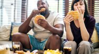 Overweight multiracial couple eat unhealthy junk foods that cause inflammation