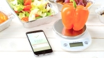 Iphone-Calorie-Counting-App-Sorrounded-By-Vegetables-And-Orange-Pepper-On-Food-Scale