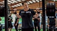 Prowrestler John Cena setting up a back squat exercise at a squat rack