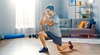Male-Performing-Split-Squat-In-Living-Room-Home-Gym