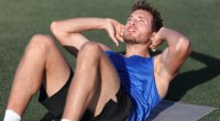 Man-Doing-Crunches-On-Astro-Turf