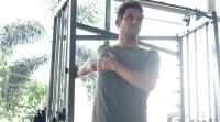 Fit man stretching his shoulder and chest against gym machine