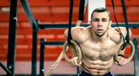 Muscular-Male-Gymnast-Performing-Ring-Chest-Flye