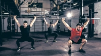 Three fit men squatting with empty barbell bar