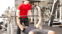 Two-Young-Males-Working-Out-Spotter-Barbell-Bench-Press