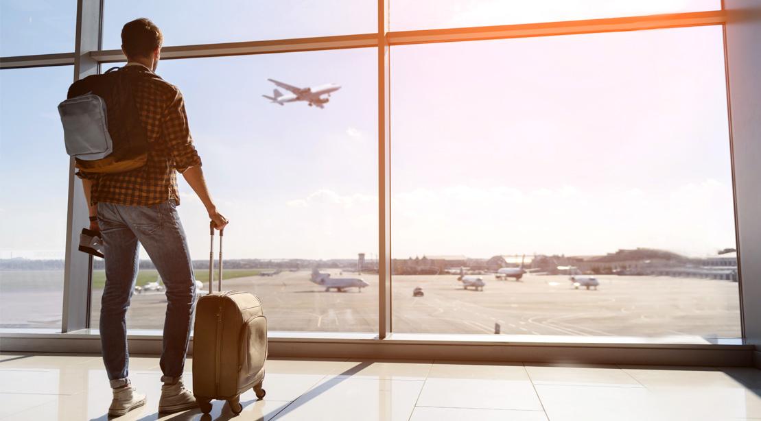 Young-Man-At-Airport-Baggage-Looking-At-Airplane