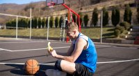 Basketball athlete eating a banana on an outdoor basketball court