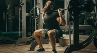 Bearded weight lifter struggling with a squat at smith machine