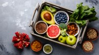 Box containing healthy foods fruits and vegetables nuts