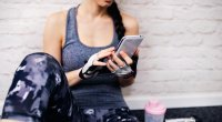 Women in fitness clothes sit against the wall on the smartphone