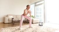 Female-In-Pink-Athletic-Gear-Practicing-Squatting-In-Living-Room-Streaming-Programs