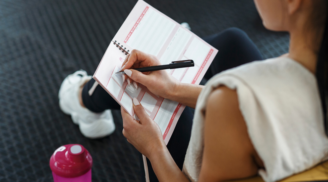Female-Writing-Workout-Plan-In-The Gym