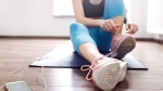 Fit-Female-In-Fitness-Clothes-Tying-Sneakers-At-Home