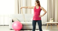 Fitness-Woman-Working-Out-At-Home-With-Bands-And-Swiss-Ball