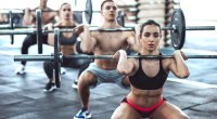 A group of physically fit people attending a group fitness class performing a lightweight front squat