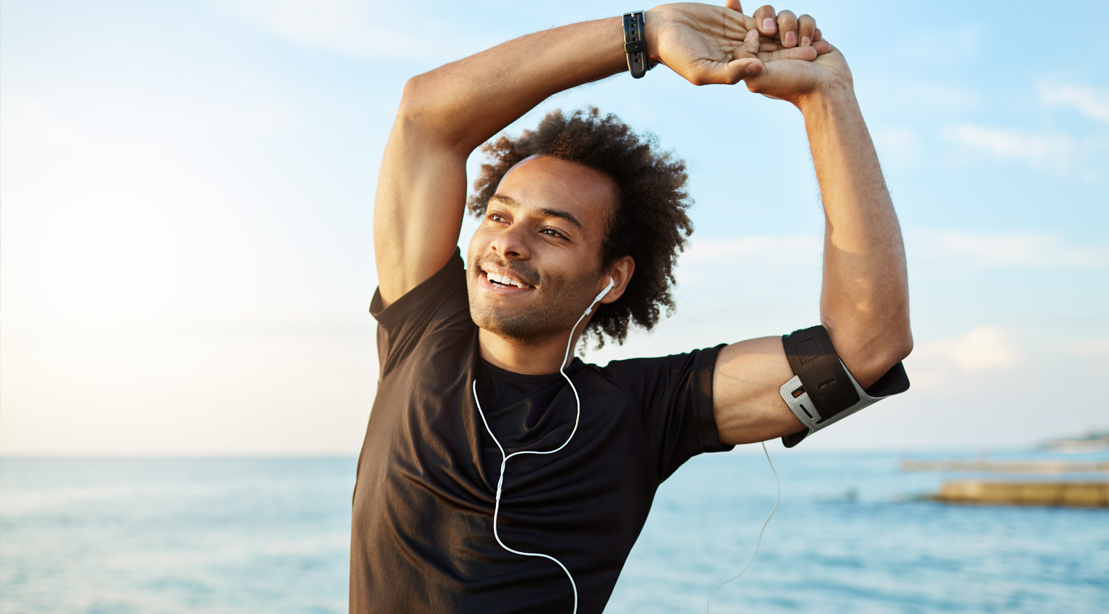 Happy-Fit-Man-Stretching-and-exercise-is-medicine-While-Listening-To-Ear-Phones