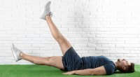 Happy man doing bodyweight exercise called the flutter kick exercise