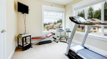 Home-Gym-Room-Filled-With-Exercise-Equipment-Overlooking-Suburbia