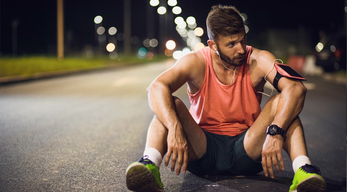 Male-Jogger-Resting-In-Middle-Of-Road-At-Night