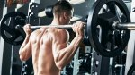 Man building bigger muscles at a Smith Machine doing a barbell back squat exercise