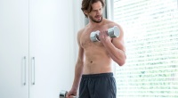 Fitness man doing bicep curls with light weight dumbbells