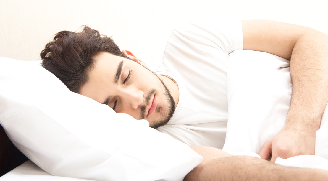 Man sleeping deeply and comfortably on his sides of the bed