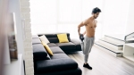 Man-Stretching-Quads-In-Home-Living-Room
