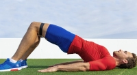 Man Wearing Fitness Gear Performing Glute Bridge Exercise Outdoors