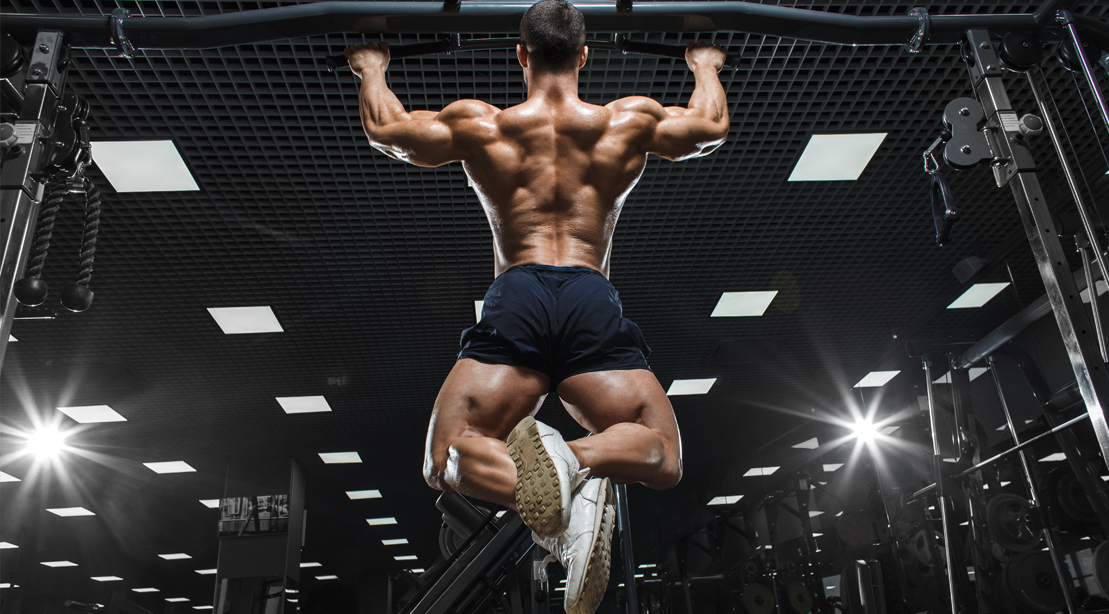 Man working out his muscular back with a pullup exercise
