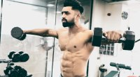 Male fitness model performing dumbbell side lateral raise exercise