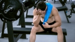 Muscular-Man-With-Shirt-Off-Looking-Sick-At-Bench-Press-Gym