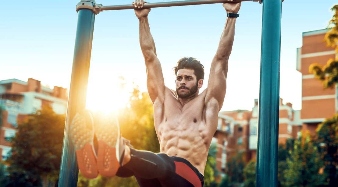 Muscular man working out his abs outdoors with hanging leg raises exercise