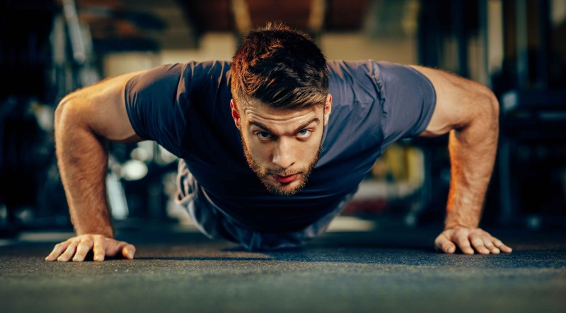 bearded man doing chest workout with a pushup exercise