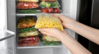 Person-Holding-Bag-Of-Frozen-Corn-In-Front-Of-Fridge