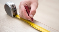 Person-Measuring-Tape-Cutting-Wood