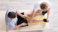 Physical-Therapist-Helping-Man-With-Banded-Row-Exercise