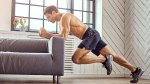 Shirtless Man Exercising In Living Room Against A Couch