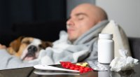 Sick-Man-With-Dog-Drugs-Medicine-And-Thermometer-On-Table