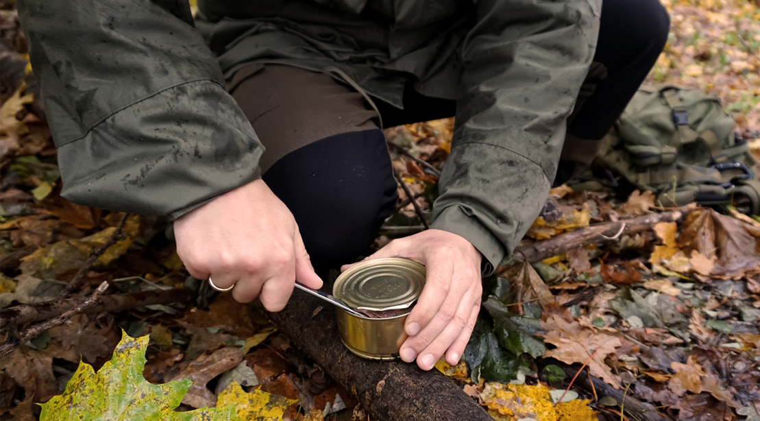 Survival-Camper-Opening-Can-Food-With-Pocket-Knife