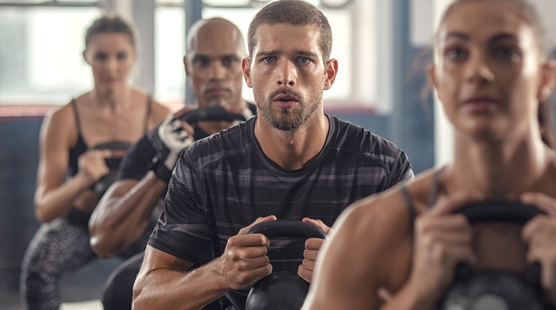 Sweaty-Confused-Man-In-Group-Fitness-Class-Performing-Kettlebell-Squat