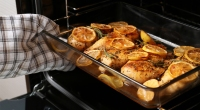 Taking-Broiled-Chicken-Breast-With-Lemon-Slices-Out-Of-The-Oven