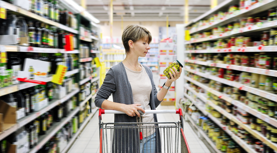 Woman-Looking-At-Jar-Of-Olives-In-Grocery-Store-Aisle