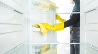 Woman-Wearing-Rubber-Gloves-Cleaning-Refridgerator