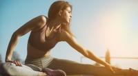 Young-Fitness-Female-Stretching-Legs-In-Sunset