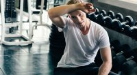 Young man sitting on bench next to a dumbbell rack wiping sweat from his forehead after a workout